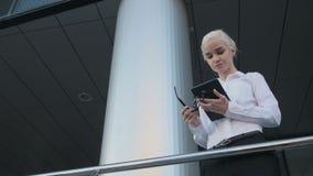 Portrait de la belle femme d'affaires à l'aide de la tablette en dehors du centre Images libres de droits