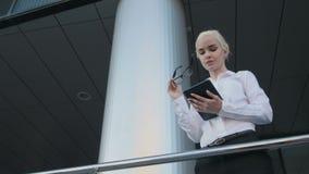Portrait de la belle femme d'affaires à l'aide de la tablette en dehors du centre Photo libre de droits