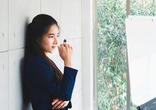 Portrait de la belle femme d'affaires de jeunes longs cheveux asiatiques dans le costume de bleu marine pensant dans le bureau mo photo stock