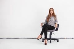 Portrait de la belle femme d'affaires s'asseyant sur la chaise contre le wh image stock