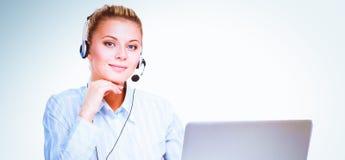 Portrait de la belle femme d'affaires travaillant à son bureau avec le casque et l'ordinateur portable photos libres de droits