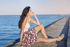 Portrait de la belle femme de sourire parlant au téléphone se reposant sur une jetée de mer Photo stock