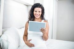 Portrait de la belle femme enceinte à l'aide du comprimé numérique Photographie stock