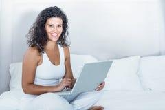 Portrait de la belle femme enceinte de sourire à l'aide de l'ordinateur portable Photo libre de droits