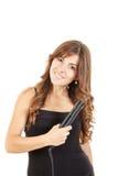 Portrait de la belle femme à l'aide du redresseur de cheveux Images stock