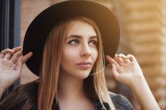 Portrait de la belle fille à la mode utilisant le chapeau noir à large bord élégant recherchant Style de vie de ville toned Photographie stock libre de droits