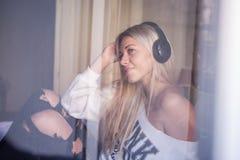 Portrait de la belle fille avec des écouteurs écoutant la musique pop Images stock