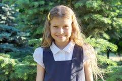 Portrait de la belle fille blonde de sourire 7, 8 années, enfant dans l'uniforme scolaire Jour lumineux ensoleillé de fond image libre de droits