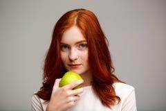 Portrait de la belle fille de gingembre tenant la pomme au-dessus du fond gris Photos libres de droits
