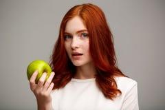 Portrait de la belle fille de gingembre tenant la pomme verte au-dessus du fond gris Image libre de droits