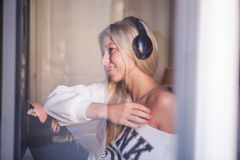 Portrait de la belle fille heureuse avec des écouteurs écoutant la musique pop Photo stock