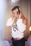 Portrait de la belle fille heureuse avec des écouteurs écoutant la musique pop Photographie stock