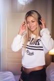 Portrait de la belle fille heureuse avec des écouteurs écoutant la musique rock Photos stock