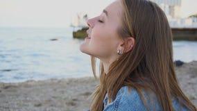 Portrait de la belle fille qui respire l'air marin salé, se reposant sur la plage de la plage sablonneuse la soirée fraîche d'été banque de vidéos