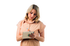 Portrait de la belle jeune écriture blonde de femme sur un bloc-notes, fond blanc d'isolement images stock
