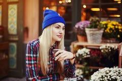 Portrait de la belle jeune dame élégante s'asseyant en café de rue et café potable Hippie avec le vieux rétro appareil-photo Photo libre de droits