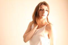 Portrait de la belle jeune femme avec la longue pose brune de cheveux d'isolement sur le fond blanc Image stock