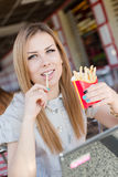 Portrait de la belle jeune femme blonde mangeant des pommes frites dans le restaurant regardant l'appareil-photo Photographie stock libre de droits