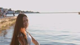 Portrait de la belle jeune femme dans la robe blanche par la mer banque de vidéos