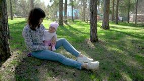 Portrait de la belle jeune femme de sourire et de son petit bébé s'asseyant sur l'herbe contre le parc d'été et le soleil verts d banque de vidéos
