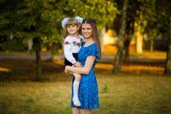 Portrait de la belle jeune mère étreignant la fille de premier-niveleuse dans l'uniforme scolaire de fête sur le parc d'automne d image libre de droits