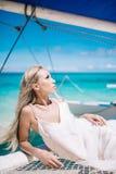 Portrait de la belle longue jeune mariée blonde de cheveux dans la robe blanche Elle s'étendent sur le voilier bleu Photos stock