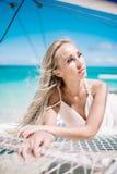 Portrait de la belle longue jeune mariée blonde de cheveux dans la robe blanche Elle s'étendent sur le voilier bleu Mer de ciel b Photos libres de droits