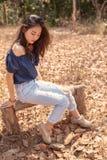 Portrait de la belle plus jeune femme asiatique s'asseyant sur le banc en bois photos stock
