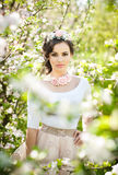 Portrait de la belle pose de fille extérieure avec des fleurs des cerisiers dans la fleur pendant une journée de printemps lumine Image libre de droits