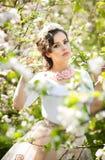 Portrait de la belle pose de fille extérieure avec des fleurs des cerisiers dans la fleur pendant une journée de printemps lumine Images libres de droits
