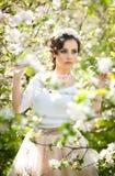 Portrait de la belle pose de fille extérieure avec des fleurs des cerisiers dans la fleur pendant une journée de printemps lumine Photographie stock