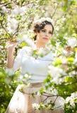 Portrait de la belle pose de fille extérieure avec des fleurs des cerisiers dans la fleur pendant une journée de printemps lumine Photos stock