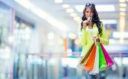 Portrait de la brune de sourire attrayante dans le centre commercial avec une carte de crédit de sacs dans une main Images stock