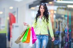 Portrait de la brune de sourire attrayante dans le centre commercial avec une carte de crédit de sacs dans une main Photographie stock libre de droits