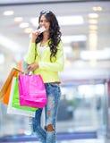 Portrait de la brune de sourire attrayante dans le centre commercial avec une carte de crédit de sacs dans une main Photo stock