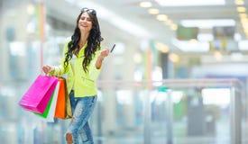 Portrait de la brune de sourire attrayante dans le centre commercial avec une carte de crédit de sacs dans une main Photographie stock