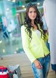 Portrait de la brune de sourire attrayante dans le centre commercial avec une carte de crédit de sacs dans une main Photo libre de droits