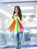 Portrait de la brune de sourire attrayante dans le centre commercial avec une carte de crédit de sacs dans une main Images libres de droits