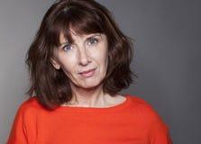 Portrait de la brune 50s magnifique avec le sourire serein pour des soins de la peau Photo libre de droits