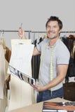 Portrait de la couturière masculine tenant l'ébauche de couture de modèle, de croquis et de conception Photo stock