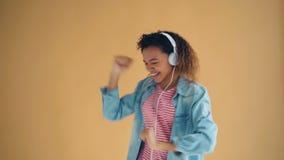 Portrait de la dame mignonne d'Afro-américain écoutant la musique dans la danse d'écouteurs clips vidéos