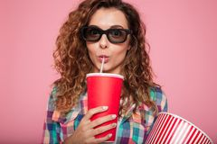 Portrait de la dame sérieuse en verres 3d buvant du kola d'isolement Photographie stock