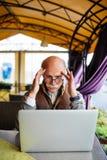Portrait de la douleur mûre de tête d'homme regardant l'ordinateur portable se reposant en café de rue pendant la coupure Image stock