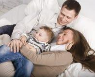 Portrait de la famille, de la maman heureuse et du papa jouant avec leur fils dans le lit Photo libre de droits