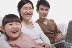 Portrait de la famille de sourire heureuse s'asseyant sur le sofa utilisant l'ordinateur portable, regardant l'appareil-photo, tir Images libres de droits