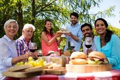 Portrait de la famille heureuse ayant les petits gâteaux et le vin rouge dans le parc Image libre de droits