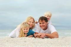 Portrait de la famille heureuse de quatre personnes détendant sur la plage photographie stock libre de droits