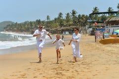 Portrait de la famille heureuse mignonne courant sur la plage sablonneuse photographie stock libre de droits