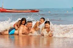 Portrait de la famille heureuse mignonne prenant un bain de soleil sur la plage sablonneuse pendant l'été images libres de droits
