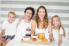 Portrait de la famille heureuse prenant le petit déjeuner sur le lit Image stock